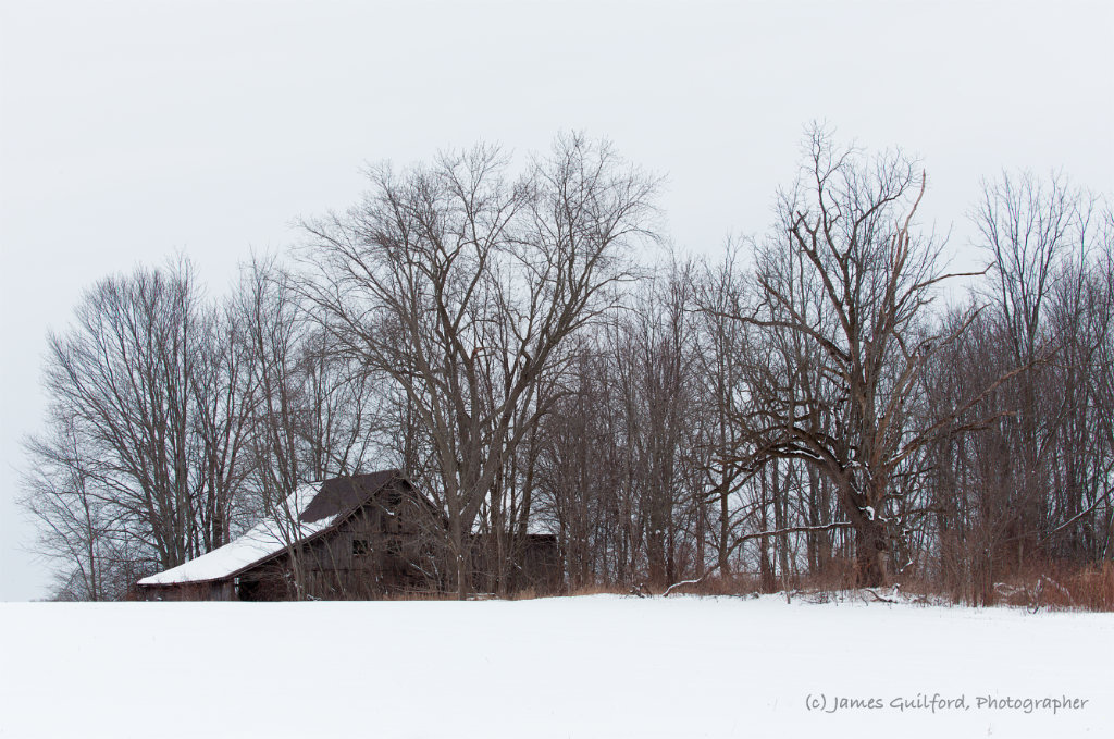 Photo: Derelict barn in a snowy field. Photo by James Guilford.