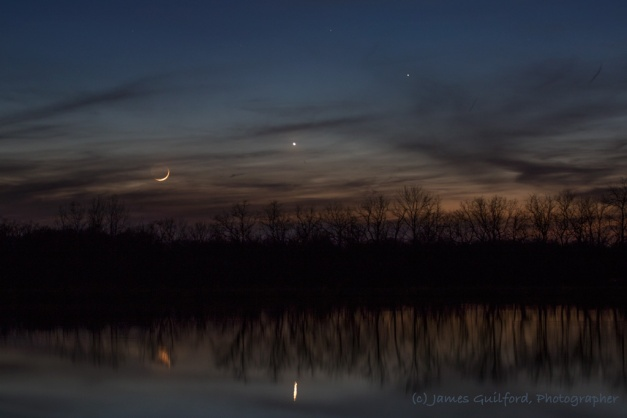 Photo: Parting Shot. The Moon, and Company, sink into clouds and trees to disappear for the night, their light reflected in dark lake waters. Photo by James Guilford.
