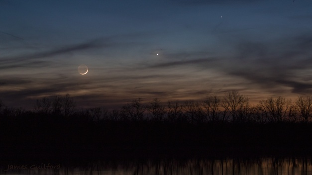Photo: Colors of Twilight. Left to right: Moon, Venus, and Mercury, in conjunction, sink in the tree-edged western sky. Photo by James Guilford.