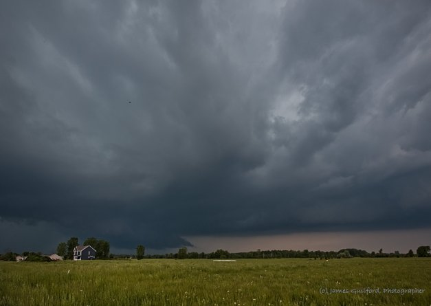 Photo: Storm clouds over a house and flat field. Photo by James Guilford.