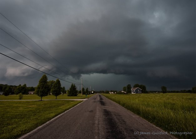 Photo: Storm clouds over a country road. Photo by James Guilford.