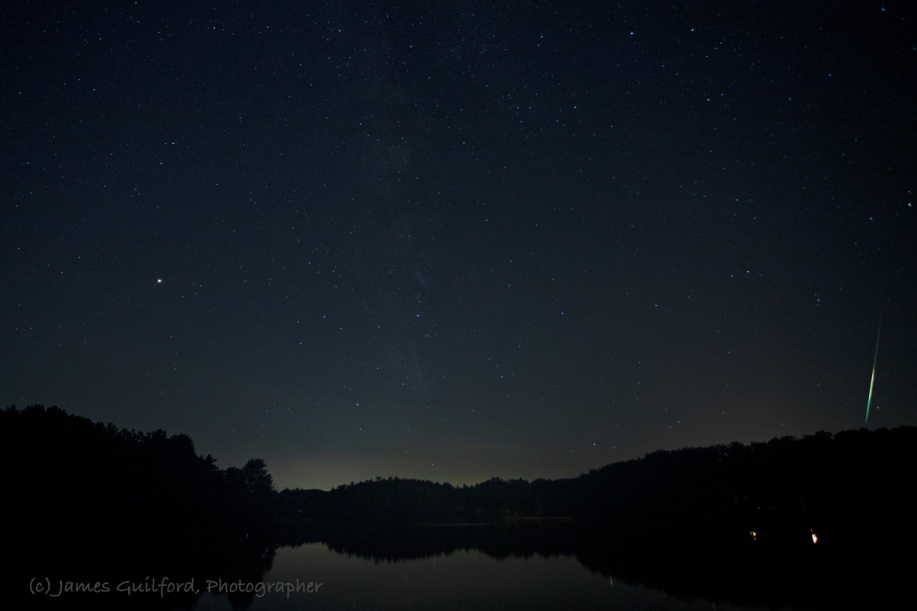 Photo: Here is an extremely bright, and very slow fireball just within the right edge of the frame. I remember the streak appearing warm in color, yellowish, but the camera recorded the spectral colors you see here. The lights near the bottom of the picture are artificial lights onshore, not reflections of stars. Photo by James Guilford.