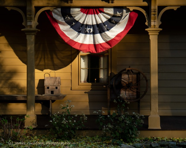 Photo: Times Remembered. Rustic items sit on a porch under patriotic bunting lit by late-day sun. Photo by James Guilford