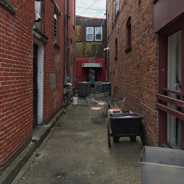 Photo: Grungy alleyway with patio seating. Photo by James Guilford.