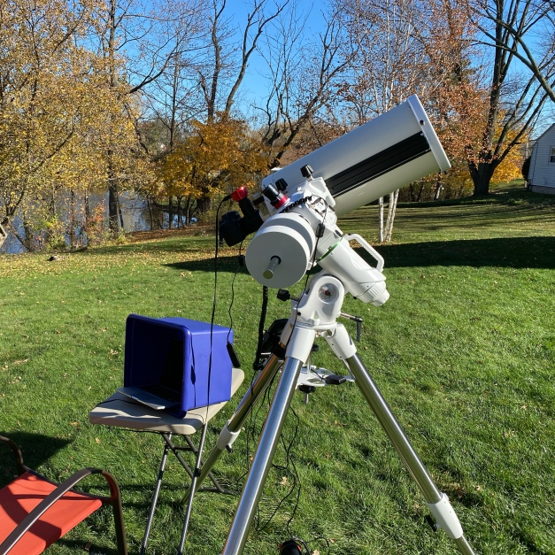 Photo: Telescope set up for solar imaging. The Canon EOS 6D Mk. 2 camera is in silhouette at the base of the scope while the little red ASI planetary camera rides above it. The blue box shades a laptop computer for use with the ASI.